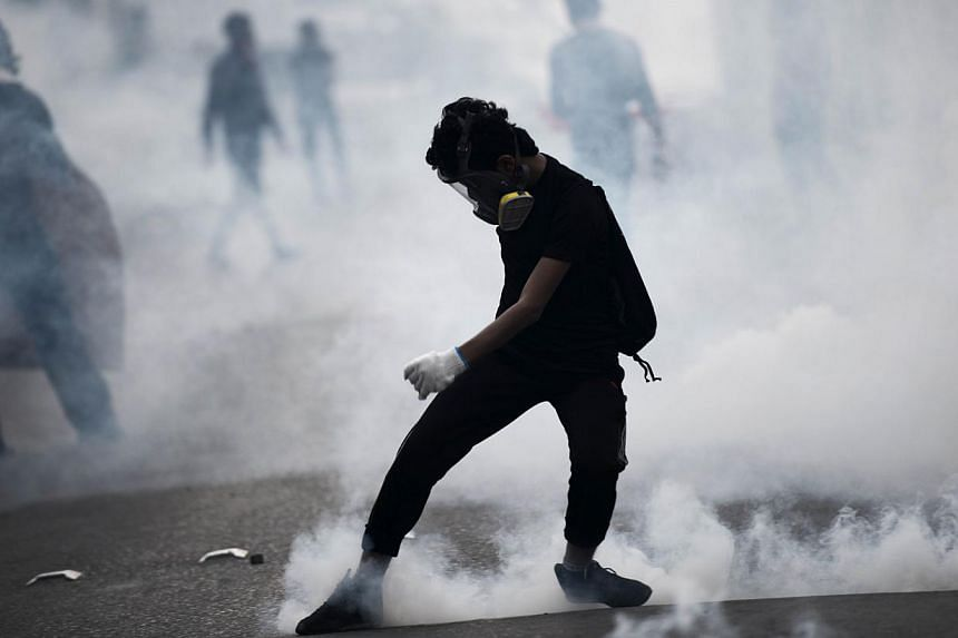 A Bahraini protester kicking back a tear gas canister during clashes with riot police following a protest against the arrest of the head of the banned Shi'ite opposition movement Al-Wefaq, Sheikh Ali Salman, on Jan 1, 2015 in Bilad al-Qadeem, a subur