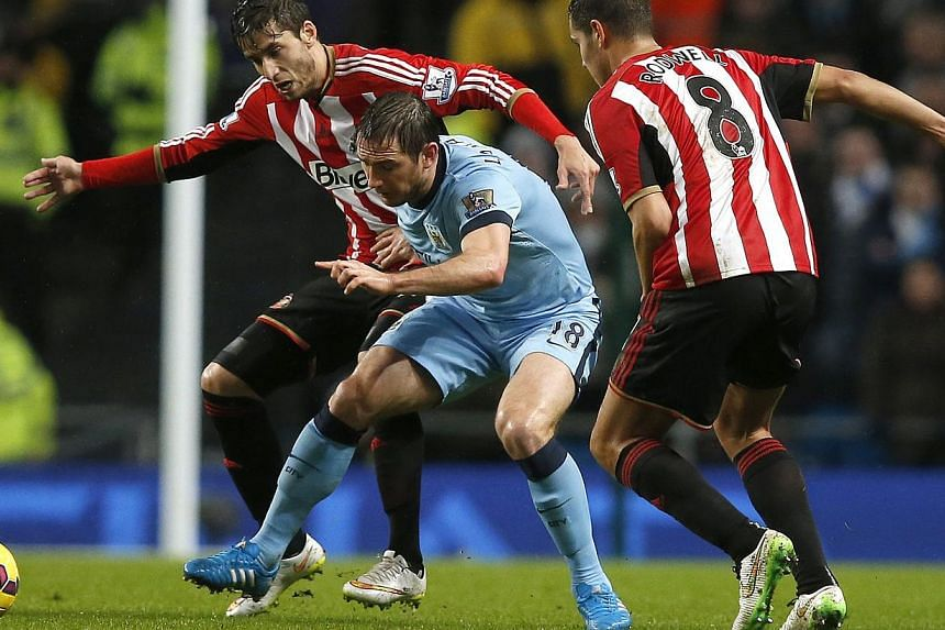 Manchester City's Frank Lampard (centre) is challenged by Sunderland's Ricardo Alvarez (left) and Jack Rodwell during their English Premier League soccer match at the Etihad Stadium in Manchester, northern England Jan 1, 2015. -- PHOTO: REUTERS