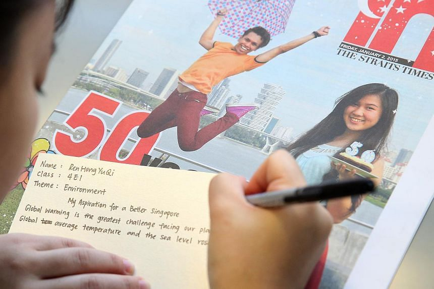 A Yio Chu Kang Secondary School student pens her aspiration for a better Singapore on the theme of environment during a CCE lesson using the Jubilee Edition of ST IN. -- ST PHOTO: NEO XIAOBIN