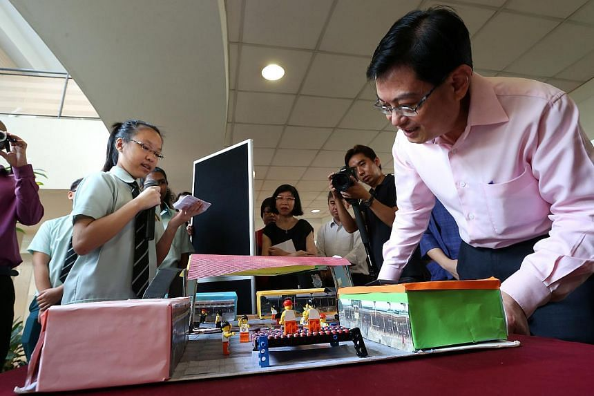 "Minister for Education Mr Heng Swee Keat (extreme, right) checks out a model of Kebun Baru Mall as Yio Chu Kang Secondary 3 student Snowi Kwan (left), 14, shares her experience in designing part of the N6 Cluster mySG Trail ""My Town, My Home – Disco"