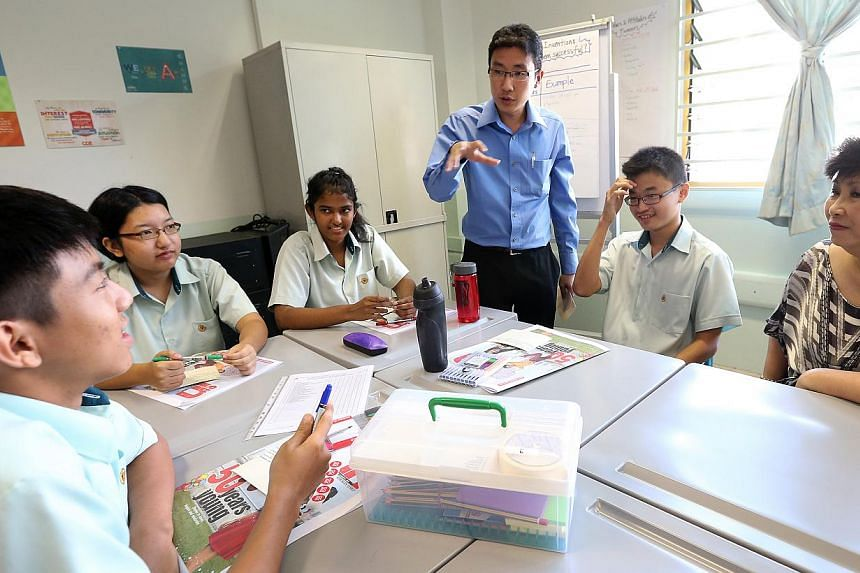 Yio Chu Kang Secondary School students interact and share their aspirations for a better Singapore during a CCE lesson using the Jubilee Edition of ST IN. -- ST PHOTO: NEO XIAOBIN