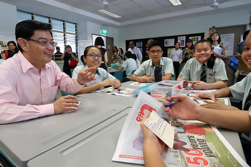 Minister for Education Mr Heng Swee Keat (left) listens as Yio Chu Kang Secondary School student Lim Zheng Long (extreme, right), 16, shares his aspiration for a better Singapore with his classmates in a CCE lesson using the Jubilee Edition of ST IN.