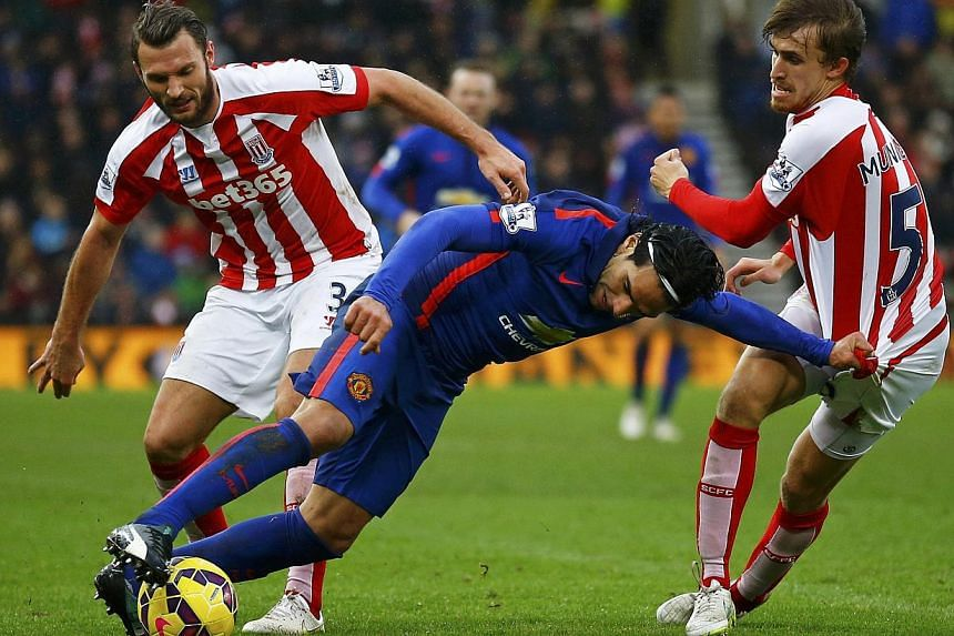 Manchester United's Radamel Falcao (centre) is challenged by Stoke City's Erik Pieters (left) and Marc Muniesa during their English Premier League soccer match at the Britannia Stadium in Stoke-on-Trent, central England Jan 1, 2015. -- PHOTO: REUTERS