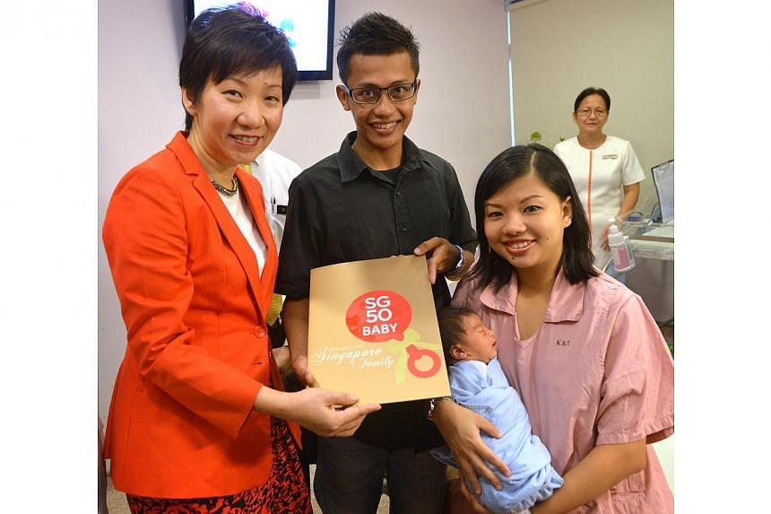 Minister in the Prime Minister's Office Grace Fu presents the first SG50 commemorative birth certificate to baby Zayn Qushairi Zulkifli and his parents. -- ST PHOTO: YEO SAM JO