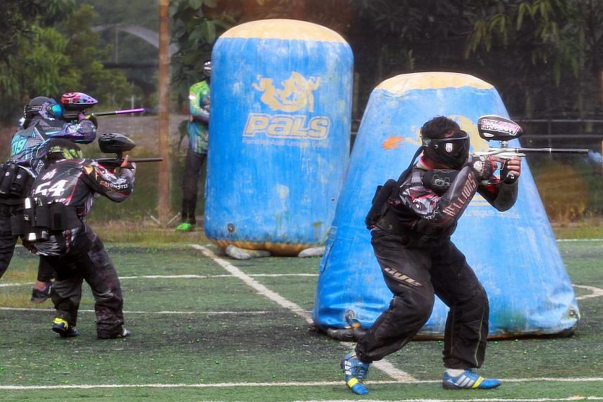 A group of people engaging in a paintball game in Singapore. Some 10,000 people from around the world have applied to be shot at as a paintball bullet tester for a British company. -- PHOTO: ST FILE