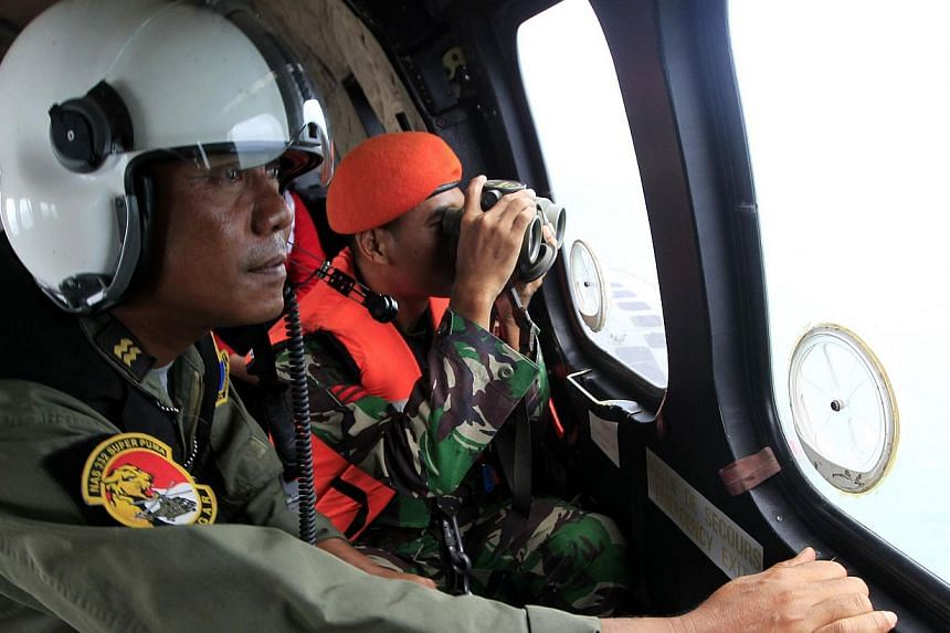 Indonesian crew members observing the surface of the sea during the search for AirAsia flight QZ8501 on board an aircraft over the Java Sea on Jan 1, 2015. -- PHOTO: AFP