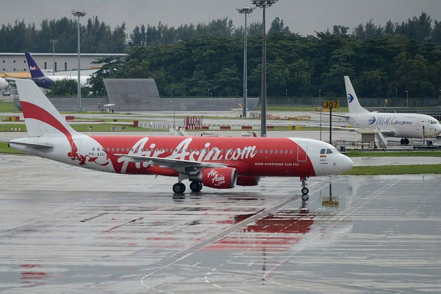 An AirAsia plane taxis on the tarmac after landing at Changi international airport in Singapore on Dec 29, 2014. -- PHOTO: AFP