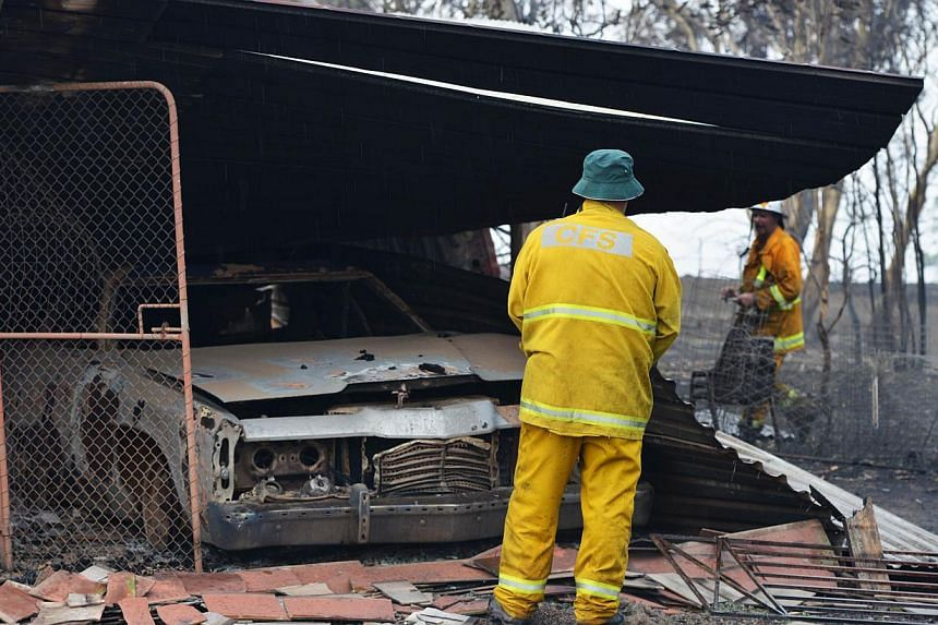 Country Fire Service volunteers work next to a burnt out shed near One Tree Hill in the Adelaide Hills, north-east of Adelaide on Jan 3, 2015. -- PHOTO: AFP