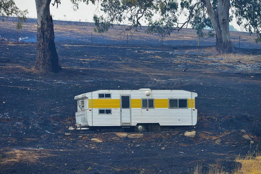 A caravan saved from the fire sits on charred earth near One Tree Hill in the Adelaide Hills, north-east of Adelaide on Jan 3, 2015. -- PHOTO: AFP