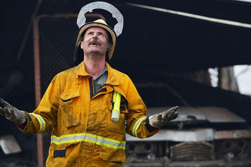 A Country Fire Service volunteer reacts as rain starts to fall near One Tree Hill in the Adelaide Hills, north-east of Adelaide on Jan 3, 2015. -- PHOTO: AFP