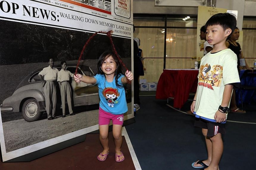 Joylene Teo (left), 5 and her brother Jovan Teo, 7attending theWalking Down Memory Lane 2015 exhibition at Jurong Green Community Club on Saturday, Jan 3, 2015.-- ST PHOTO: LAU FOOK KONG