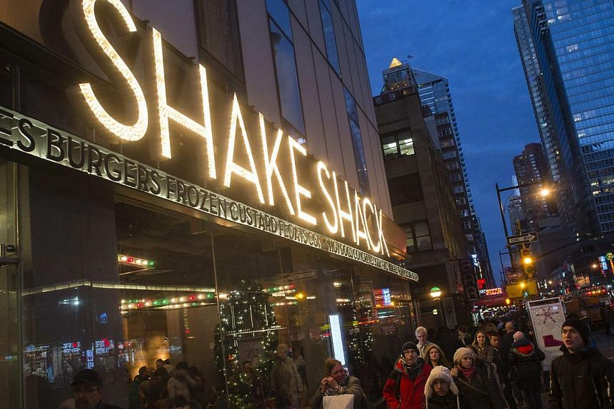 Passersby walk in front of the Shake Shack restaurant in the Manhattan borough of New York, on Dec 29, 2014. -- PHOTO: REUTERS