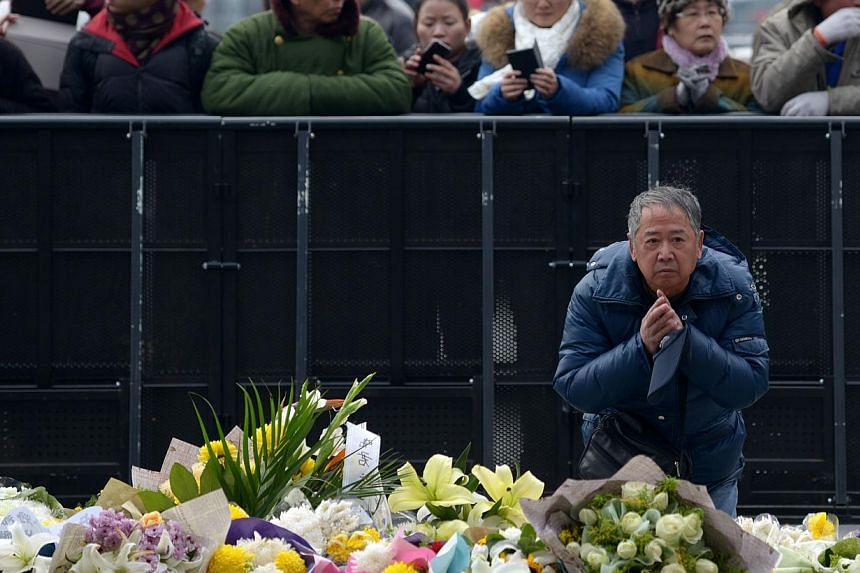 An elderly man prays for the victims at the site of the New Year's Eve stampede in Shanghai on Jan 3, 2015. -- PHOTO: AFP
