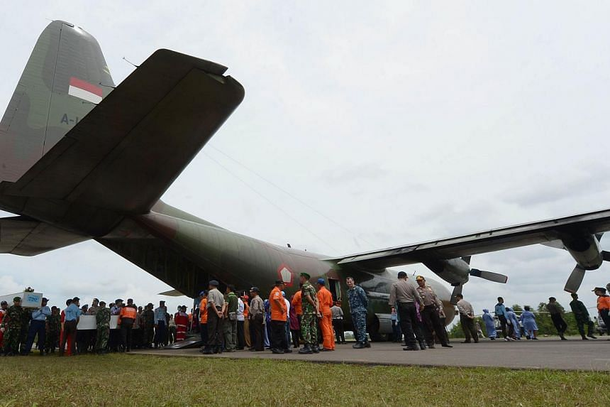 Indonesian officers carry coffins with the remains of passengers of AirAsia flight QZ8501 before being sent to Surabaya, in Pangkalan Bun on Jan 3, 2015. -- PHOTO: AFP