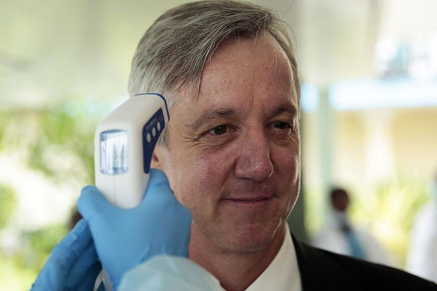 Outgoing Unmeer head Anthony Banbury getting his temperature measured during a visit to an Ebola medical unit on Dec 19, 2014. Mr Banbury said on Friday that theworld can stamp out the Ebola outbreak in West Africa by the end of the year but mo
