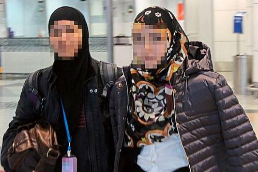 A woman officer (left) from the Bukit Aman Special Branch Counter-Terrorism Division is seen escorting the 27-year-old university dropout . -- PHOTO: THE STAR/ASIA NEWS NETWORK