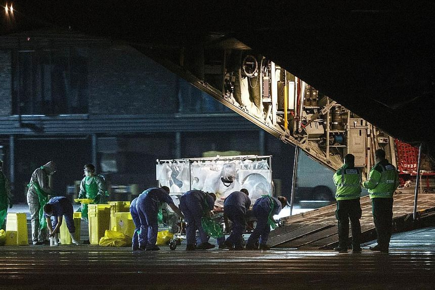 A British nursewho was diagnosed with Ebola after returning from Sierra Leone is wheeled in a quarantine tent trolley onto a Hercules Transport plane at Glasgow International Airport on Dec 30, 2014. -- PHOTO: AFP