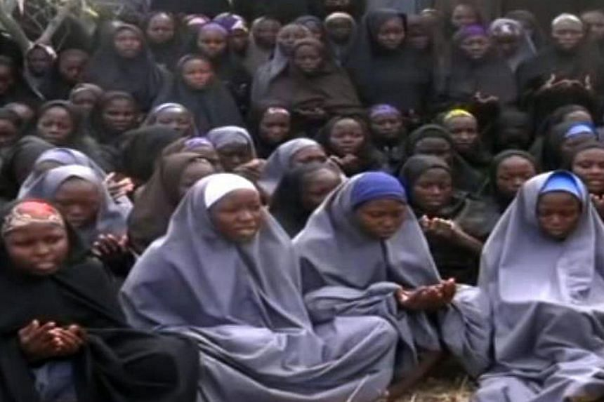 A screen grab taken on May 12, 2014 from a video of Nigerian Islamist extremist group Boko Haram shows girls wearing the full-length hijab and praying in an undisclosed rural location. The parents of 200 Nigerian schoolgirls kidnapped by Islamist reb
