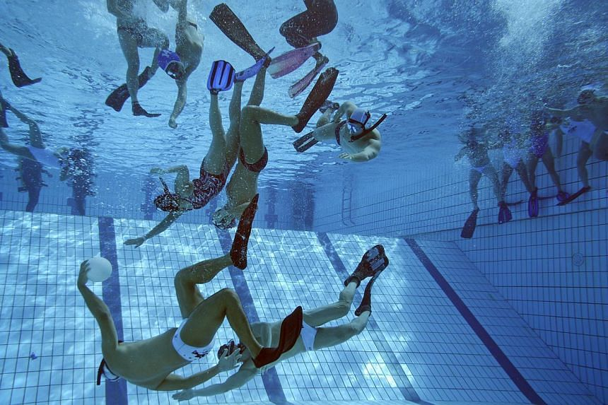 Players tussle for the ball as substitutes (right) wait at the side of the pool during a training match at Queenstown Swimming Complex on Dec 12, 2014. -- ST PHOTO: MARK CHEONG