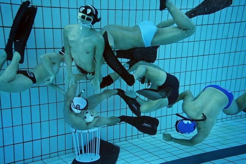 The goalkeeper attempts to protect the goal as other players try to gain possesion of the ball during an underwater rugby training session. -- ST PHOTO: MARK CHEONG