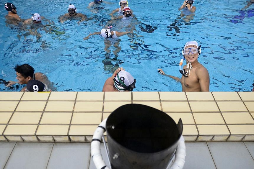 Players from the First Asian Team Underwater Rugby (Singapore) (FATUWR) relax in the pool after a training session at Queenstown Swimming Complex on Dec 6, 2014. -- ST PHOTO: MARK CHEONG