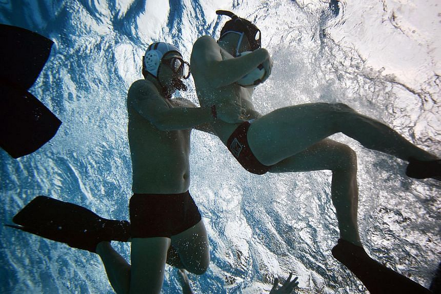 A player attempts to hold on to the ball as another tries to tackle him during an underwater rugby training session at Queenstown Swimming Complex on June 14, 2014. -- ST PHOTO: MARK CHEONG