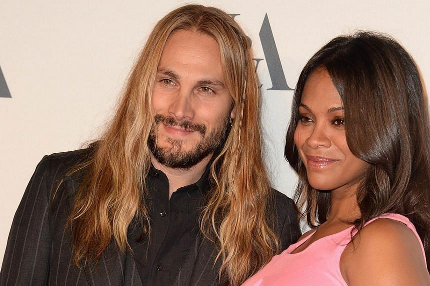 """Actress Zoe Saldana and husband, Marco Perego, arrive at a cocktail reception to celebrate the opening of the multimedia exhibition """"Hollywood Costume,"""" in this Oct 1, 2014, file photo in Los Angeles.Saldana announced Friday she had given birth"""