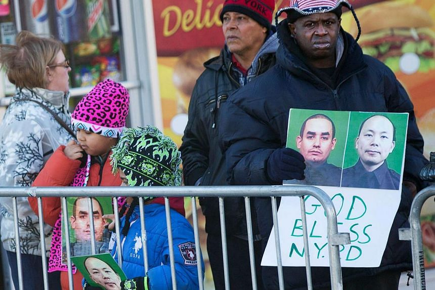 People attend the wake of New York City police officer Rafael Ramos at Christ Tabernacle Church on Dec 26, 2014, with one man (right) holding a banner featuring slain officers Ramos (left) and Wenjian Liu, whose wake is being held this weekend. -- PH