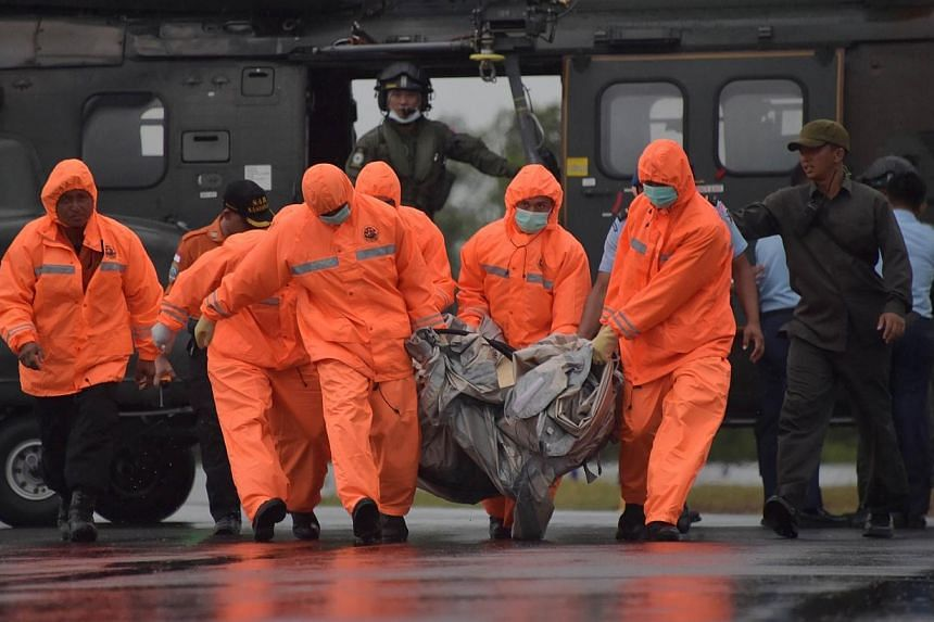 Members of an Indonesian search and rescue team carry items for investigation, found during the search operation for the missing AirAsia flight 8501, after being delivered by a Singapore Super Puma helicopter from the Republic of Singapore Air Force