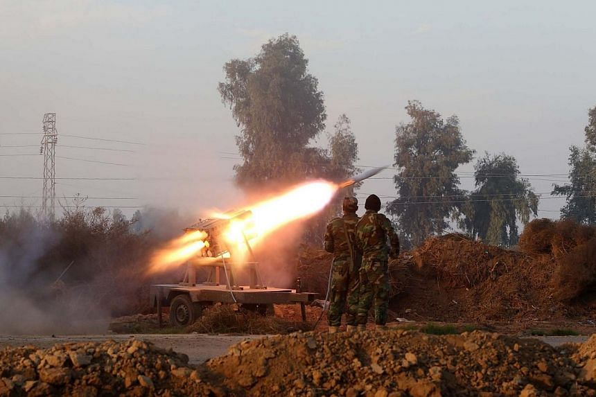 Iraqi soldiers launch a rocket during clashes against the Islamic State in Iraq and Syria (ISIS) near Dujail, some 70km north of Baghdad on Jan 2, 2015.Australian Prime Minister Tony Abbott visited Baghdad on Sunday, Jan 4, for talks on aiding