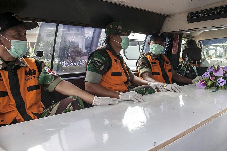 Indonesian officers sit next to a coffin contained a dead body of passenger of the AirAsia QZ8501 in Surabaya on Jan 3, 2015. -- PHOTO: AFP