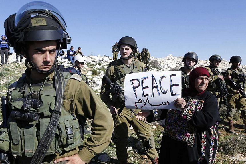 A protester holds a placard as she stands next to Israeli soldiers during a protest against Israeli settlements in Beit Fajjar town south of the West Bank city of Bethlehem on Dec 27, 2014.Israel will not permit its soldiers to be hauled in fro