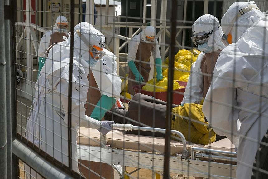 """British health workers lift a newly admitted Ebola patient onto a wheeled stretcher in to the Kerry town Ebola treatment centre outside Freetown on Dec 22, 2014.Ending the deadliest Ebola outbreak in history is """"within our reach"""", the UN's new"""