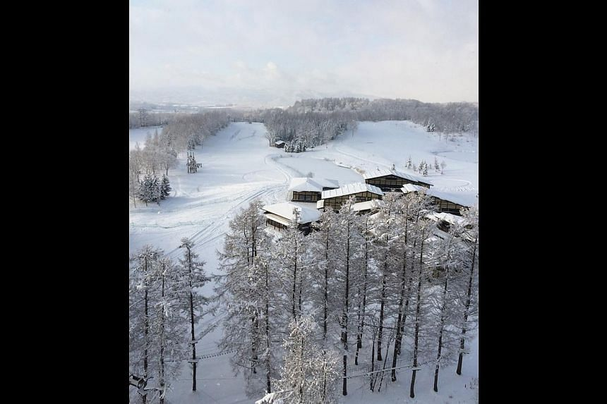 Deep snow makes Niseko a perfect spot for skiing (left). The powdery white landscape (top) of the Japanese town. Chairlifts (above) take skiers to the top of the snowy slopes. The outdoor onsen (above) at the Hilton Niseko Village and the pond fronti