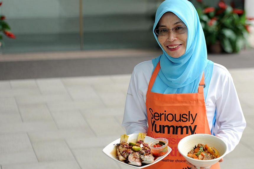 Madam Normalis Selamat shows how to cook healthier version of Malay dishes such as ikan bakar (grilled fish) and beef curry. -- ST PHOTO: TIFFANY GOH
