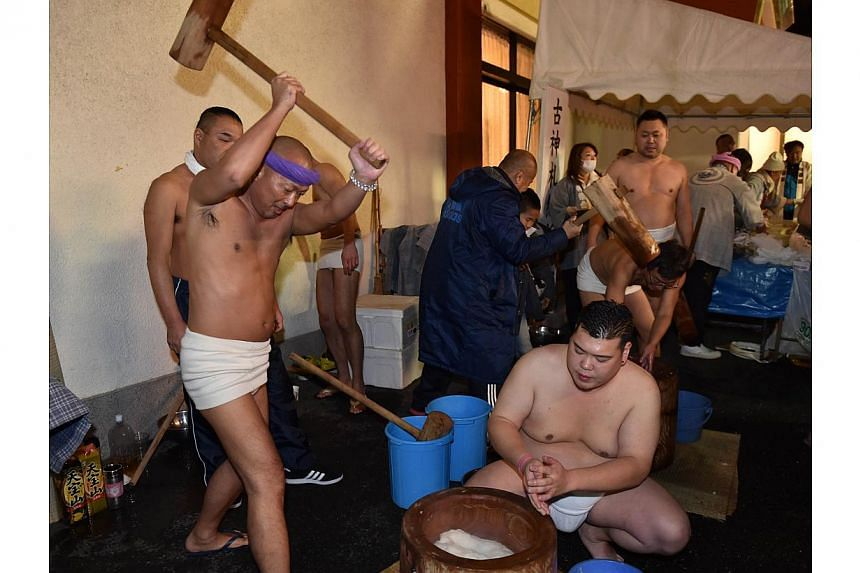 "Men in loinclothes pound steamed rice into mochi, a rice cake, to celebrate the New Year at the Kanda shrine in Tokyo on Jan 1, 2015. Nine people have choked to death in Japan after eating traditional glutinous ""mochi"" rice cakes to celebrate th"