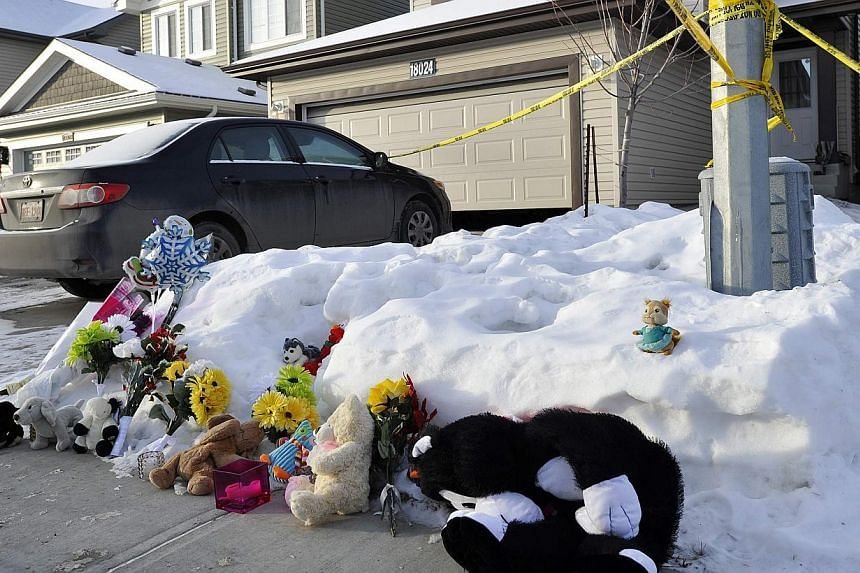 A makeshift memoria at the home where seven people were found dead in Edmonton, Alberta, on Dec 31, 2014. -- PHOTO: REUTERS