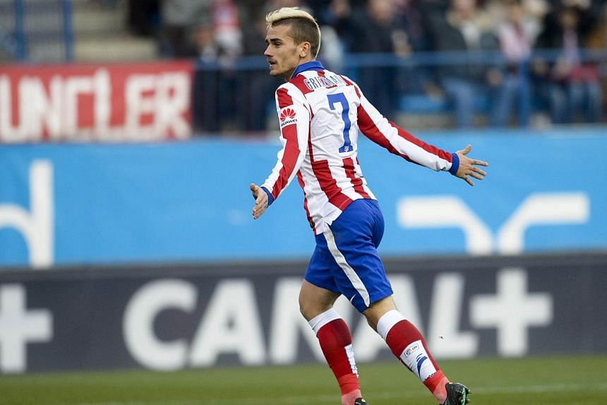 Atletico Madrid's French midfielder Antoine Griezmann celebrates his second goal during the Spanish league football match Club Atletico de Madrid versus Levante UD at the Vicente Calderon stadium in Madrid on Jan 3, 2015. -- PHOTO: AFP