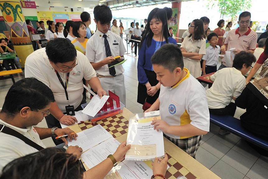 Students collecting their edusave awards at the Sembawang Edusave Awards Presentation Ceremony at Wellington Primary School on Jan 3, 2015.-- ST PHOTO:LIM YAOHUI FOR THE STRAITS TIMES