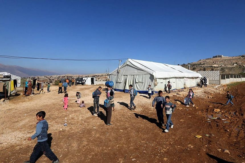 Syrian refugee children walk outside a tent being used as a school at a Syrian refugees camp in the village of Baaloul, in the west of Lebanon's Bekaa Valley on Dec 16, 2014.Lebanon is to impose visa restrictions on Syrians for the first time a