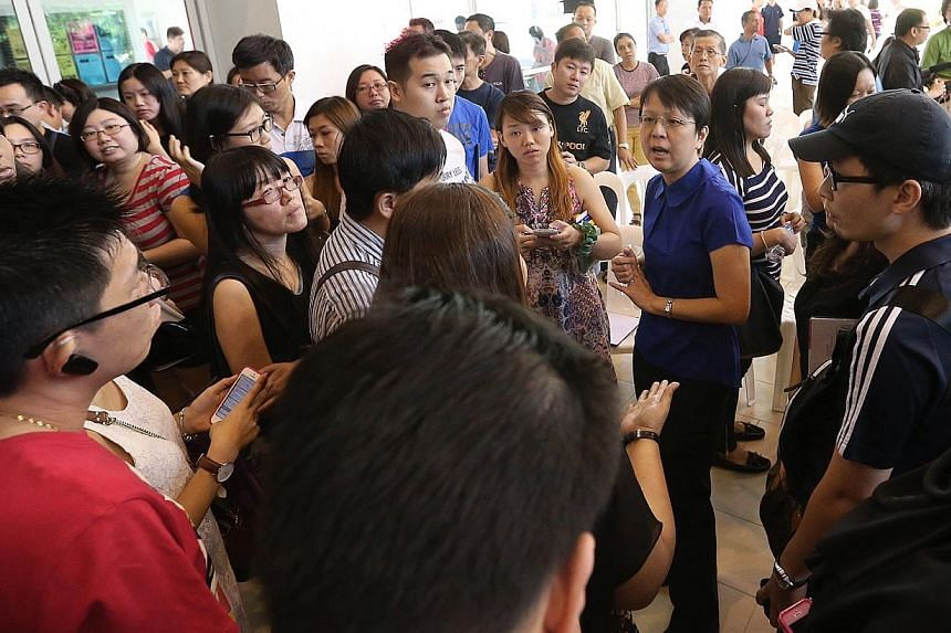 Residents speak to a HDB representative after the dialogue session held at Anchorvale Community Club's multi-purpose hallon Jan 4. 2015. -- ST PHOTO:NEO XIAOBIN