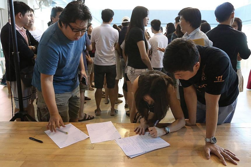Affected residents write down their names and contact information to express their interest in a full refund for their flat.-- ST PHOTO:NEO XIAOBIN