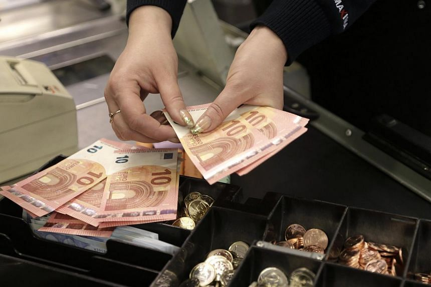 A cashier counts euro banknotes in a shop in Vilnius, Lithuania. The single currency tumbled to its lowest since early 2006 in Asia on Monday as a wave of stop-loss sales were tripped on the break of major chart support, sending the U.S. dollar flyin