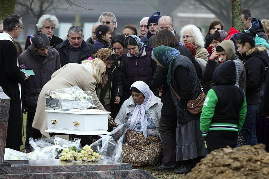 The mother of the late Maria Francesca pays homage to her baby during her funeral on Jan 5, 2015 at the Wissous cemetery.The dead baby of a Roma family at the centre of a huge racism row in France was finally laid to rest on Monday with just cl