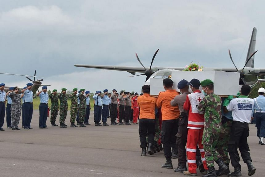 Indonesian officers carry a coffin with the remains of a passenger of the AirAsia flight QZ8501 in Pangkalan Bun on Jan 5, 2015.The airline will have to pay compensation to the next of kin of victims of the crashed flight, Indonesian officials
