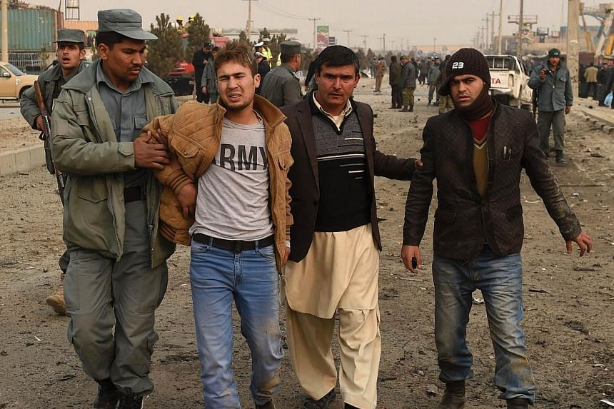 A wounded Afghan youth (2nd from left) receives assistance at the scene of a suicide attack on a European Union police vehicle along the Kabul-Jalalabad road in Kabul on Jan 5, 2015. The suicide car bombing killed at least one passer-by but did