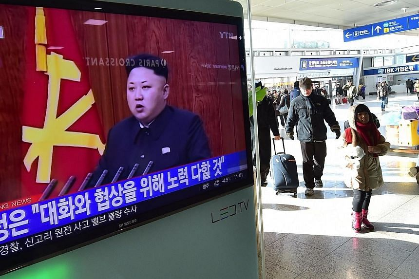 "Travellers walk past a television screen showing North Korean leader Kim Jong Un's New Year speech, at a railroad station in Seoul on Jan 1, 2015. China on Jan 5 called on ""relevant parties"" to avoid action that would escalate tension on the Kor"
