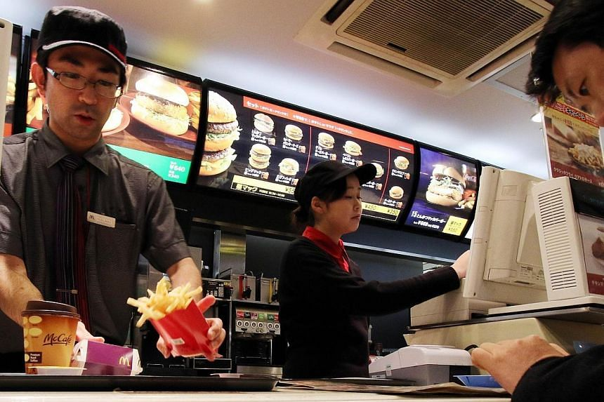 An employee serves french fries to a customer at a McDonald's restaurant in Tokyo on Dec 16, 2014.McDonald's Japan said Monday it was facing more chicken nugget woes after a customer found a piece of vinyl inside the popular menu item. -- PHOTO