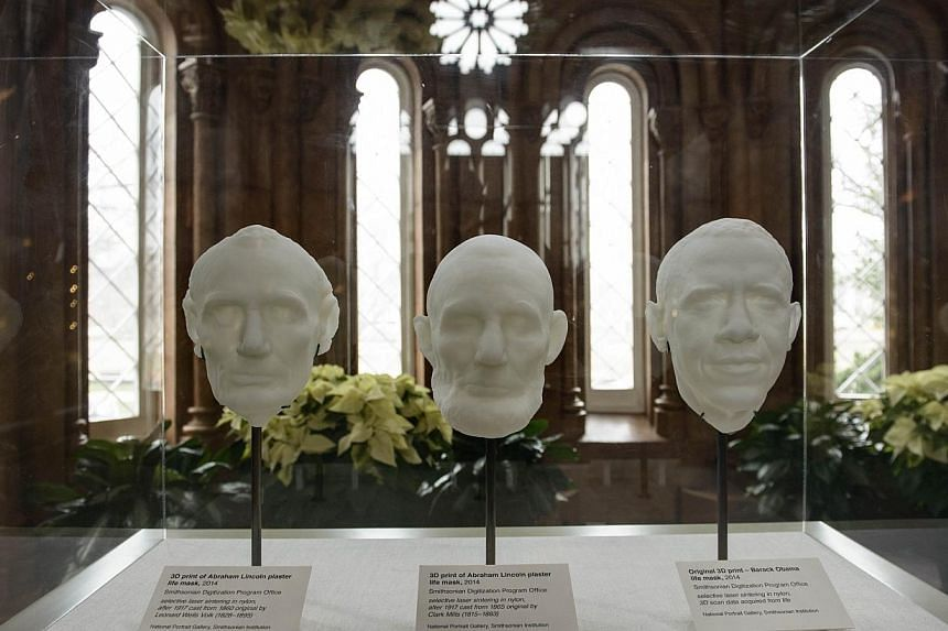 Three-D prints of a 3-D scan of former President Abraham Lincoln's life masks (left, centre) are seen with a print of a live 3-D scan of US President Barack Obama at the Smithsonian on Dec 4, 2014 in Washington, DC. -- PHOTO: AFP