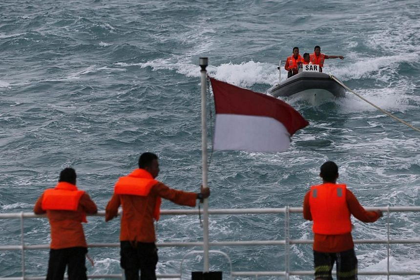 Rescue team members in a boat communicate with other members of the team on the deck of the Search and Rescue (SAR) ship KN Purworejo during a search operation for passengers onboard AirAsia Flight QZ8501 in the Java Sea on Jan 4, 2015. -- PHOTO: REU